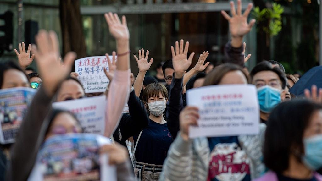 Människor i mask håller upp sina händer