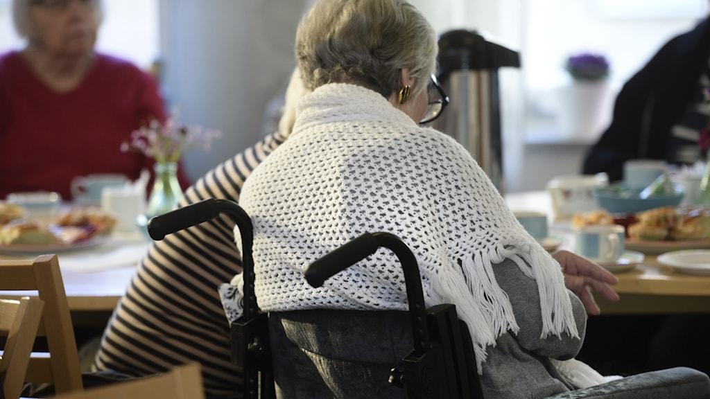 Två äldre kvinnor sitter vid ett bord med en kaffekanna.