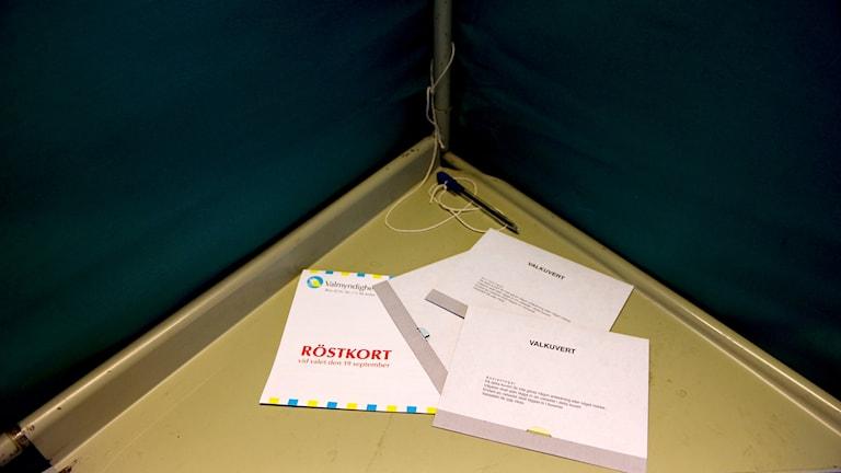 Röstkort och valkuvert i ett bås i en vallokal.