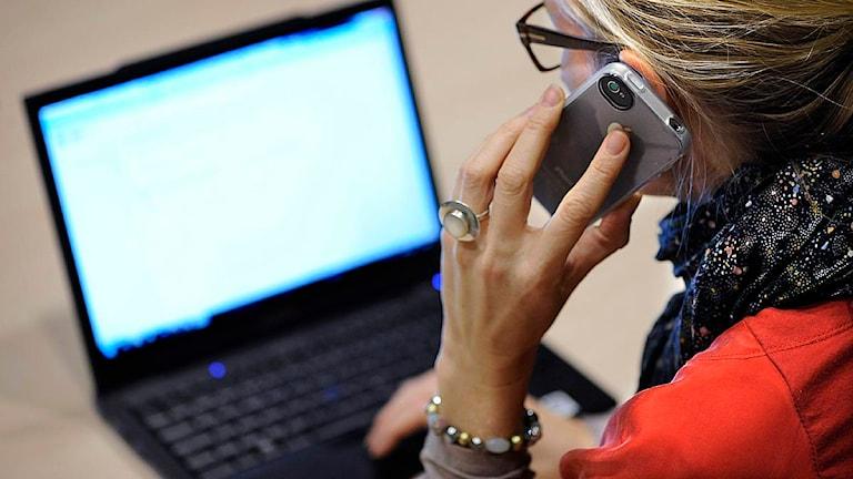 En kvinna sitter framför en laptop och pratar i mobiltelefon. Foto: Anders Wiklund/Scanpix.