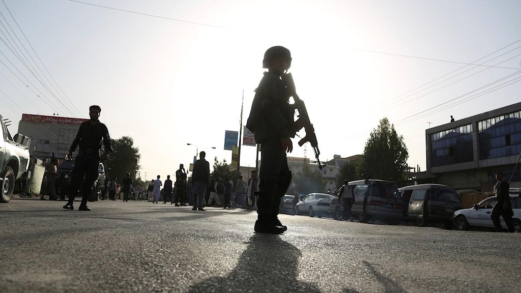 Säkerhetspersonal står på en väg med ett gevär i händerna i motljus.