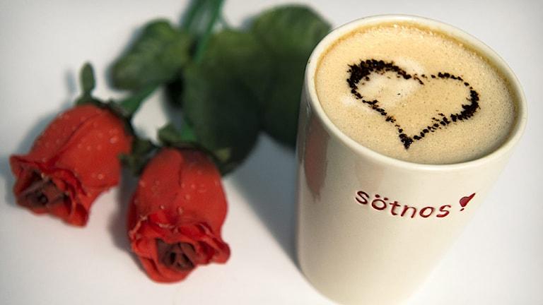 En kaffekopp med texten sötnos, ett hjärta ritat i skummet på kaffet och två röda rosor. Foto: Claudio Bresciani/Scanpix.