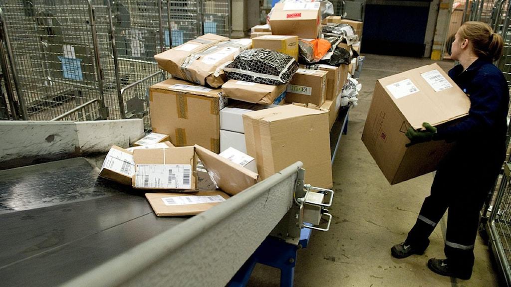 En anställd på Posten sorterar paket.