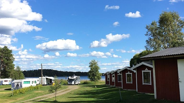 Bild på husvagnar och stugor vid sjö.