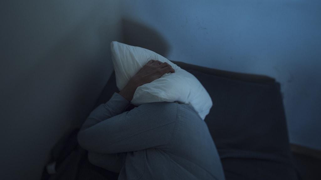 person med kudde över huvudet