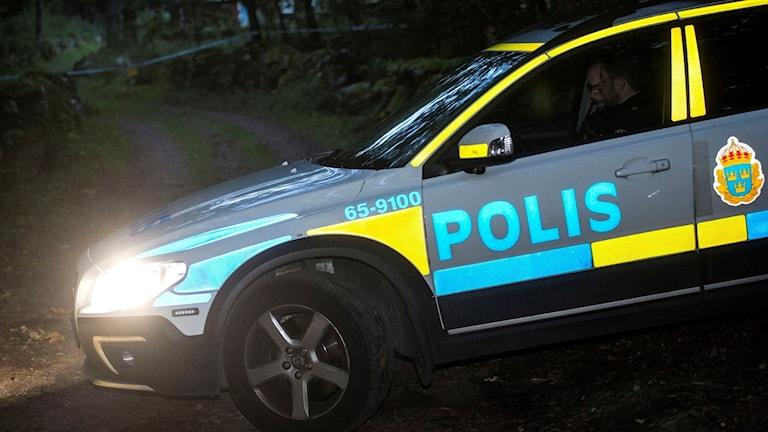 polisbil på en skogsväg i mörker. Bilden är tagen vid ett annat tillfälle.
