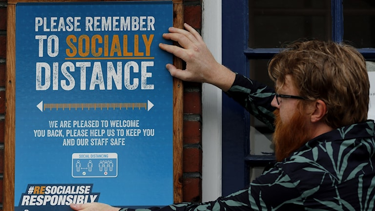 En pubägare i London sätter upp affischer med budskapet att hålla avstånd.