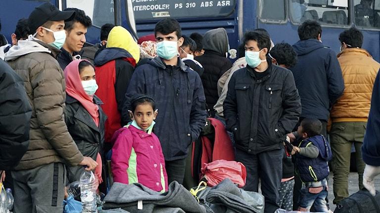 Flyktingar och migranter väntar vid en färja.