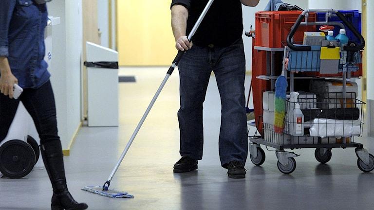 En man städar i en sjukhuskorridor.