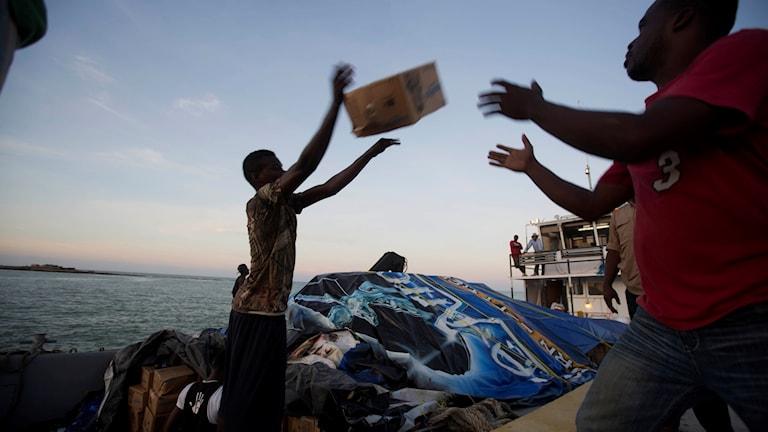 Mat och vatten lastas från båtar som anlänt till staden Jeremie.