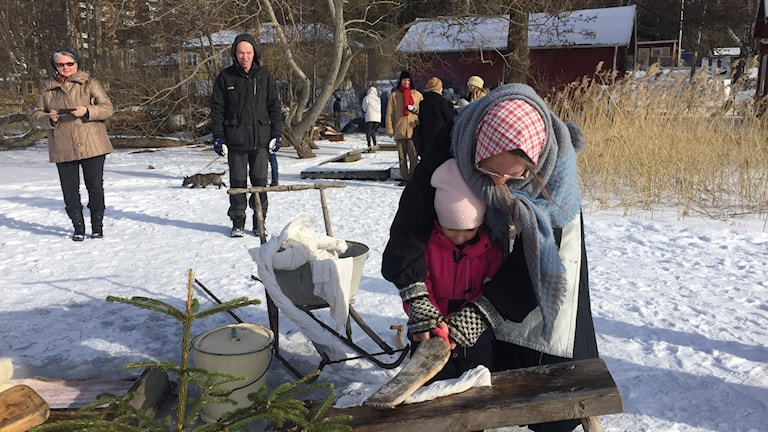 Tvätterskan Elin Magnusson lär en yngre begåvning hur man klappar tvätten.