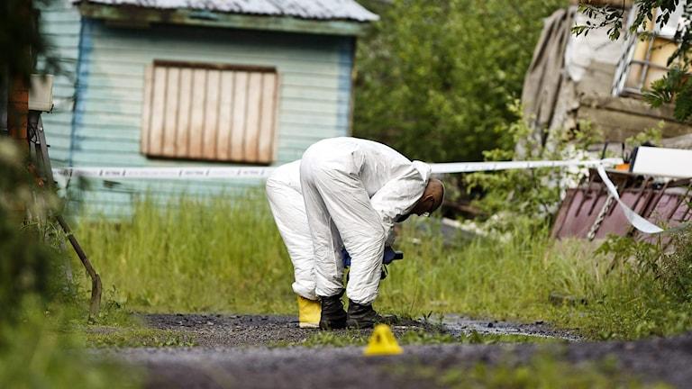 Poliser undersöker brottsplatsen i Vichti där en polis sköts till döds under en insats.