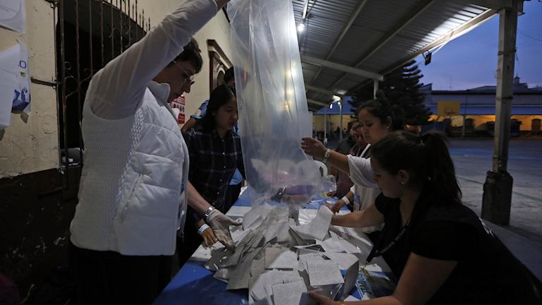 Rösträknare häller ut valsedlar på ett bord.