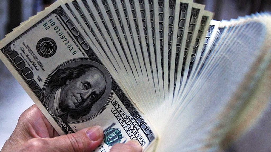 En hand som håller i sedlar.