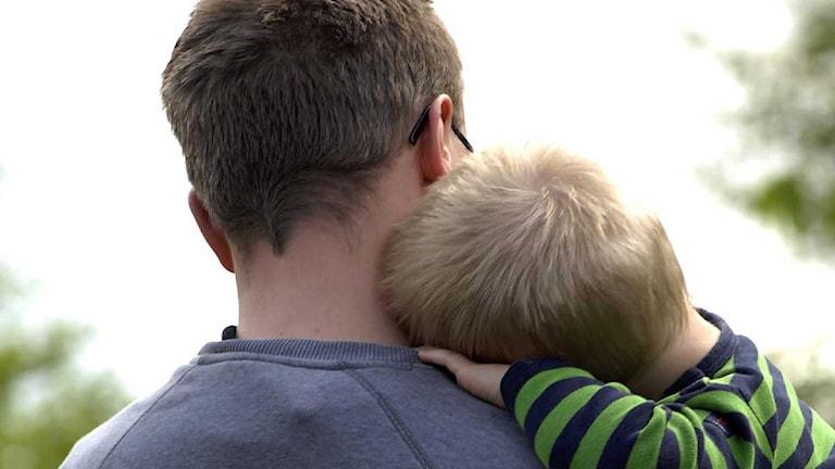 Pappa med ett barn på armen. Foto: Hasse Holmberg/Scanpix.