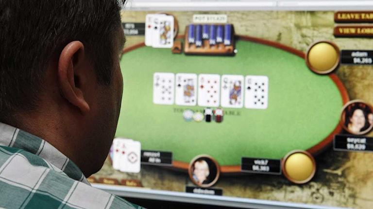 Man spelar poker hemma vid datorn.