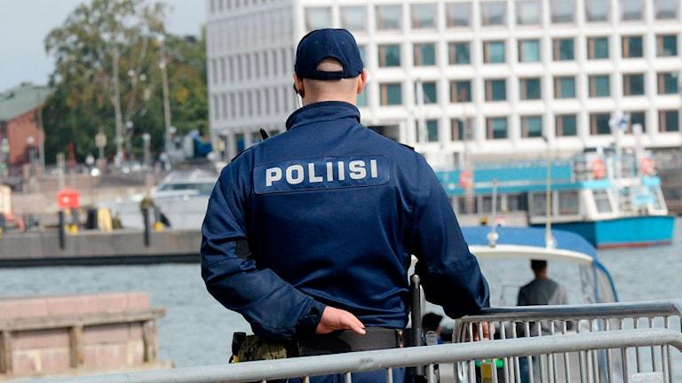 Genrebild: En finsk polis står och spanar framför ett kravallstaket.