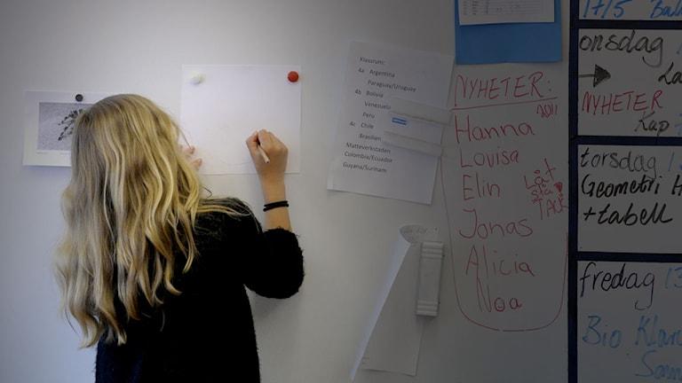En kvinna skriver något på en tavla. Foto: Janerik Henriksson/Scanpix