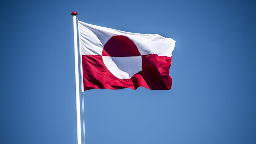 Rödvit flagga som  vajar från vit flaggstång.