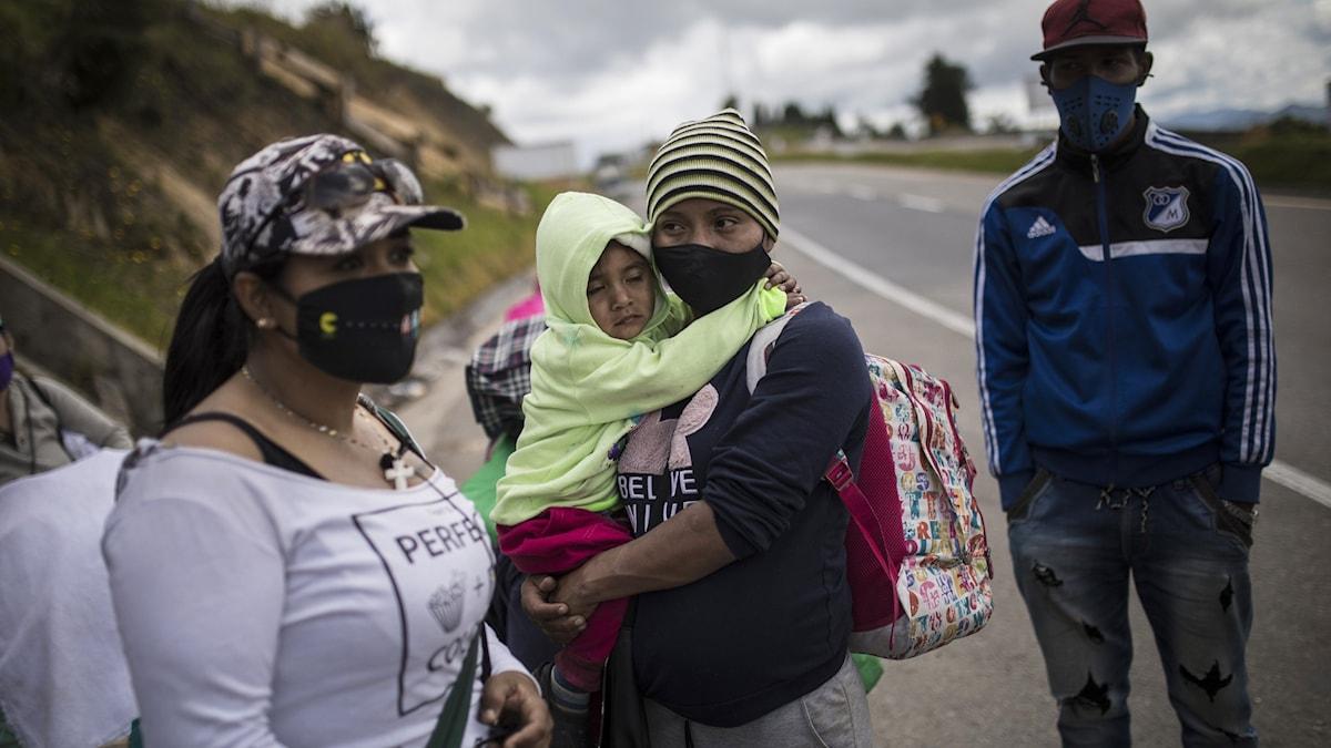 Två venezuelanska kvinnor, varav en håller ett litet barn i famnen, och en man vilar under sin vandring mot Colombias huvudstad.