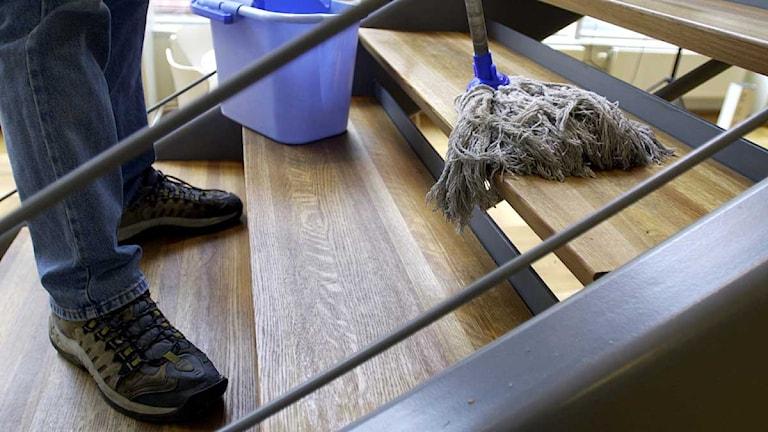 En man städar trappor med en mopp och en skurhink. Foto: Lars Pehrson/Scanpix.