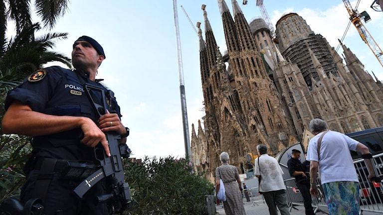 En polis står utanför Sagrada Familia.