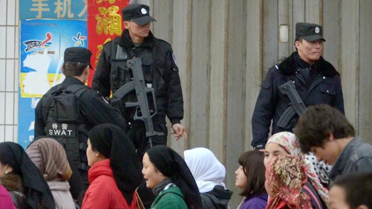 Uigurer går förbi beväpnade kinesiska poliser i Xinjiang i februari i år.