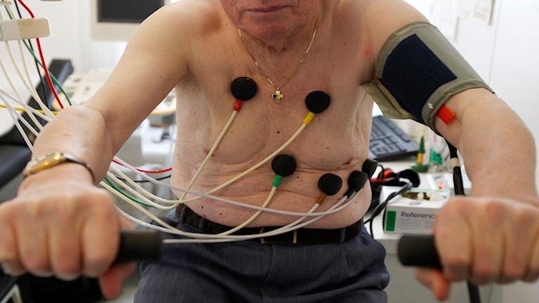 Äldre man testar sitt hjärta vid en EKG-cykel.