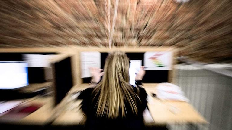 En stressad kvinna sitter vid ett skrivbord på ett kontor. Foto: Robert Henriksson/Scanpix.