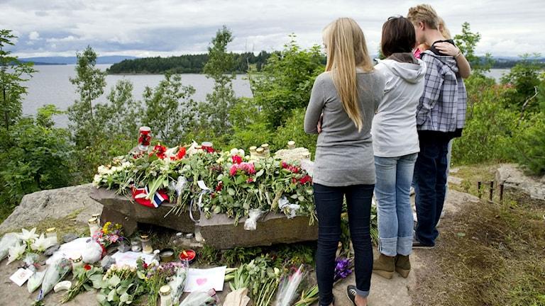 Ungdomar som står framför en hög med blommor.