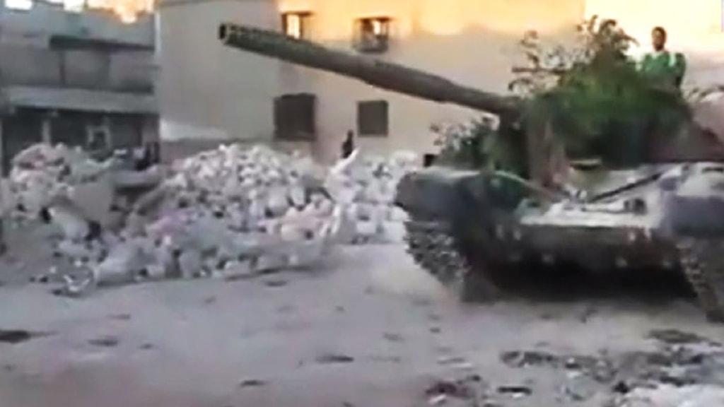 Amatörfoto som sägs föreställa en soldat ur Fria syriska armén köra ett syriskt militärfordon i staden Aleppo. Bildens äkthet kan inte bekräftas. Foto: Scanpix.