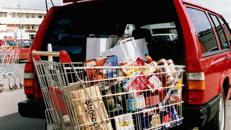 Kundvagn fylld med matvaror framför en bil med öppen bagagelucka. Foto: Tobias Röstlund/Scanpix