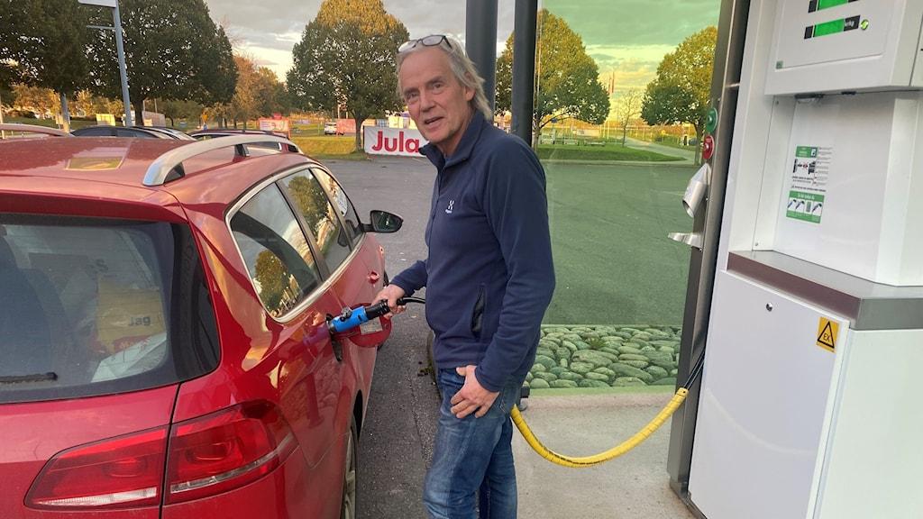 En man tankar en bil med gas.