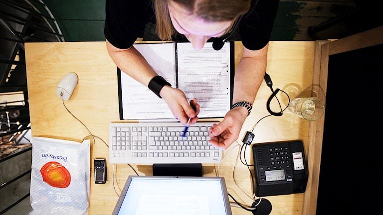 En ung kvinna sitter i telefon framför en dator.