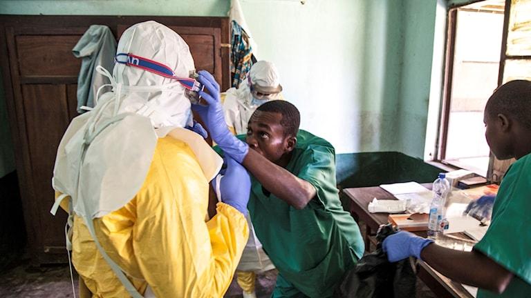 Sjukhuspersonal hjälper varandra att ta på sig heltäckande skyddsklädsel.