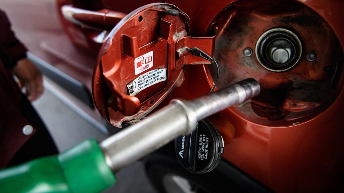 En person tankar en röd bil med bensin.