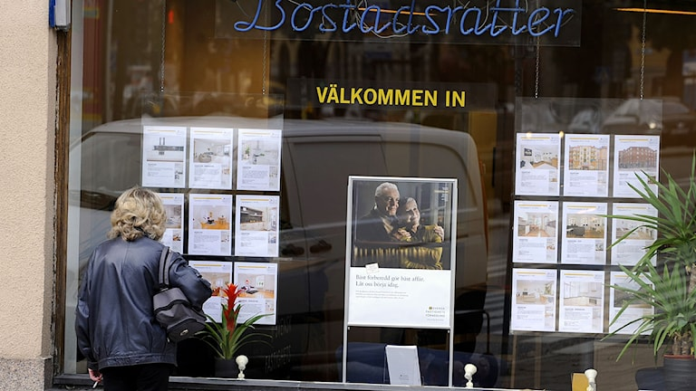 En kvinna tittar på bostadsannonser i ett skyltfönster på en bank.