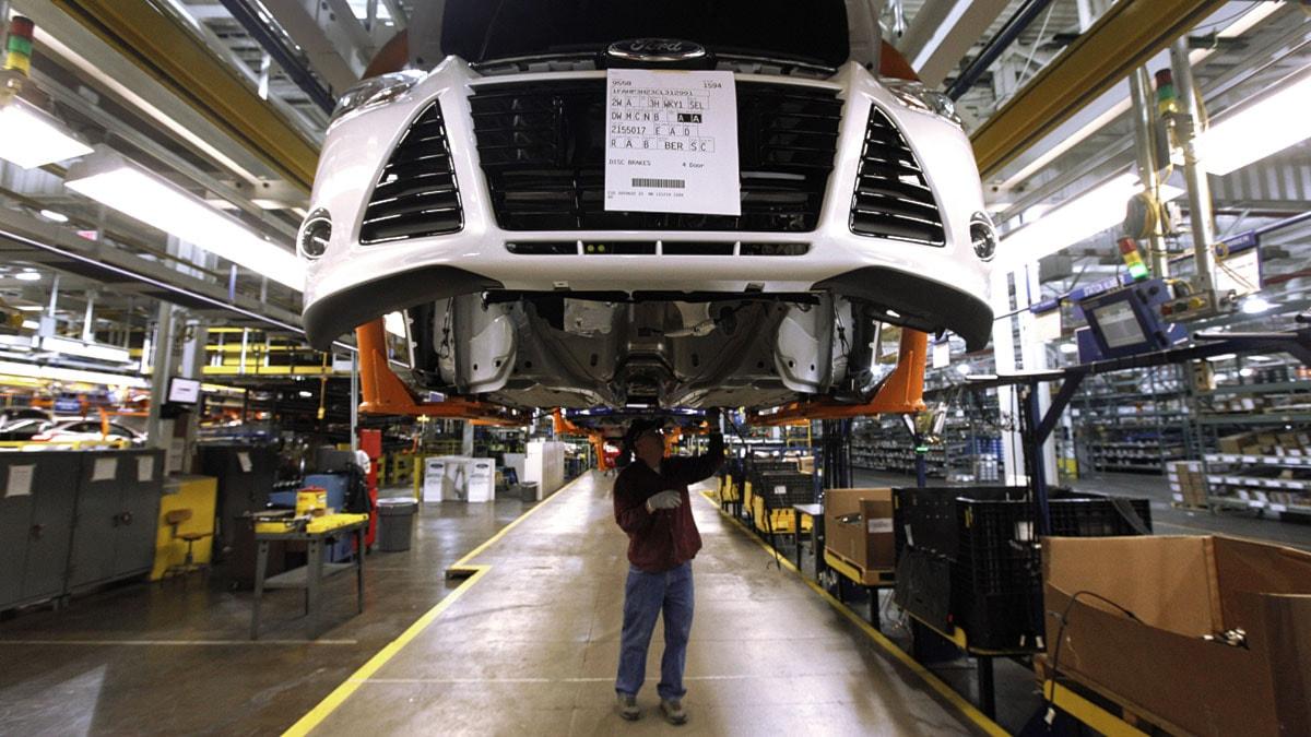 En fabriksarbetare monterar en Ford Focus på en av bilföretagets fabriker.
