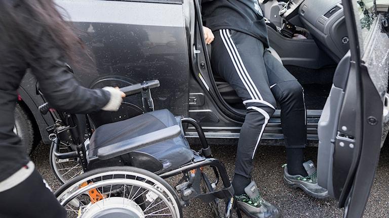 Kvinna med rullstol hjälper en man med funktionshinder att ta sig ut ur en bil.