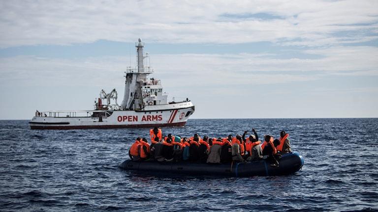 Båt med migranter framför ett räddningsfartyg.