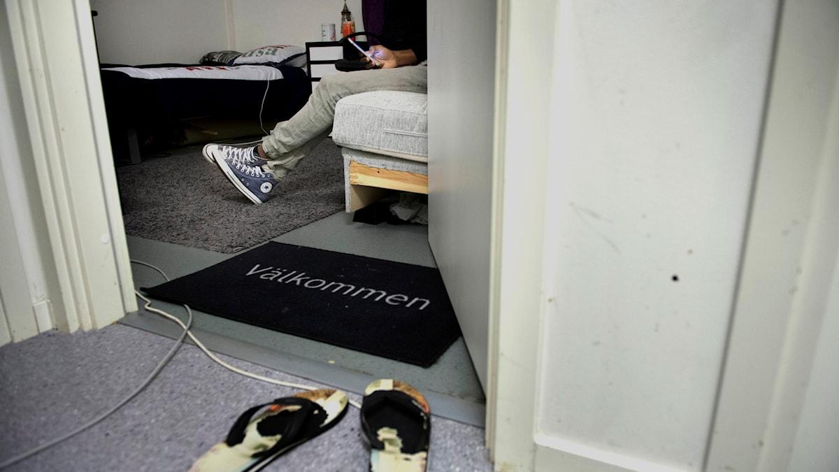"""Innanför en dörr syns en dörrmatta med texten """"Välkommen"""". Där inne sitter någon i sneekers på en sängkant med mobiltelefon i handen."""