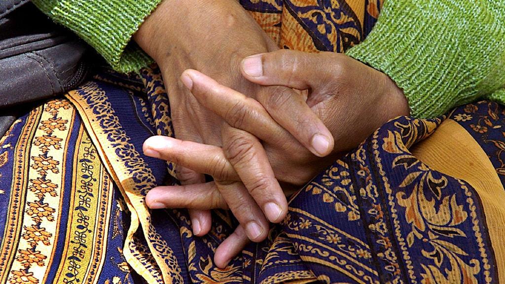 En kvinna sitter med händerna i knät.