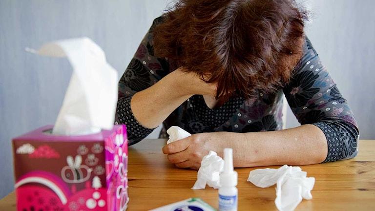 En förkyld kvinna sitter vid ett bord med pappersnäsdukar och nässpray. Foto: Jessica Gow/Scanpix.
