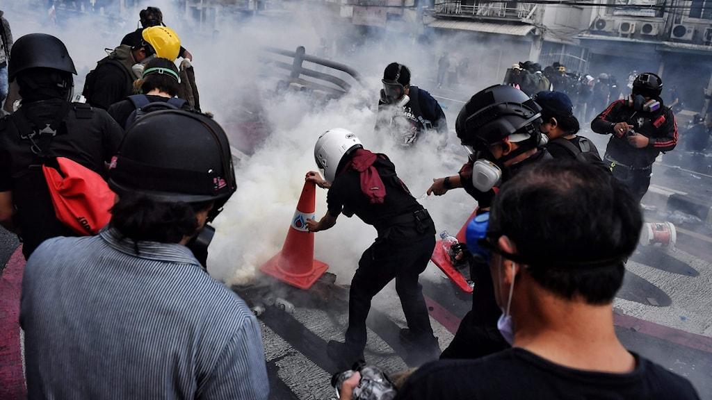 Demonstranter med hjälmar och gasmasker i Bangkok, Thailand