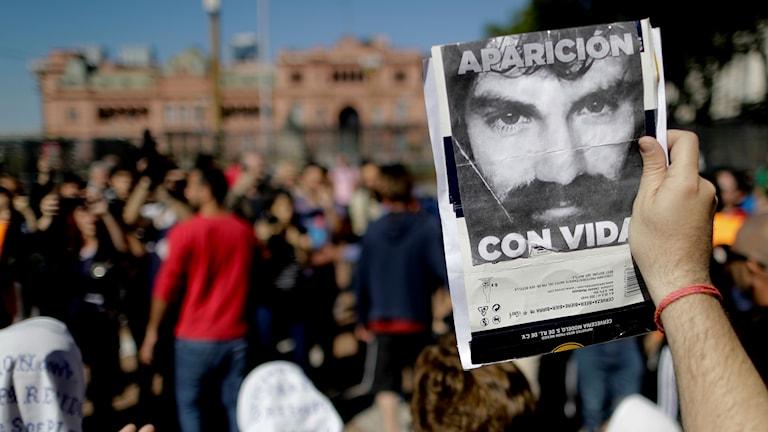 Protester och en bild på en man.