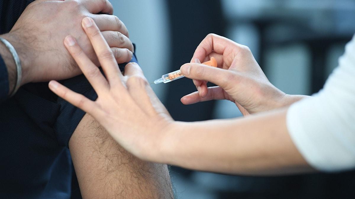 En person får en spruta med AstraZenecas vaccin i armen av vårdpersonal.