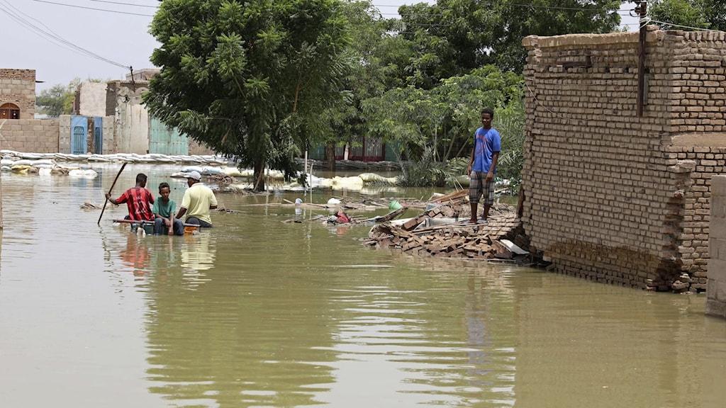 En översvämmad gata med en pojke som står och ser ut att vara fast vid ett hus, en flotte med ett gäng på närmar sig honom.