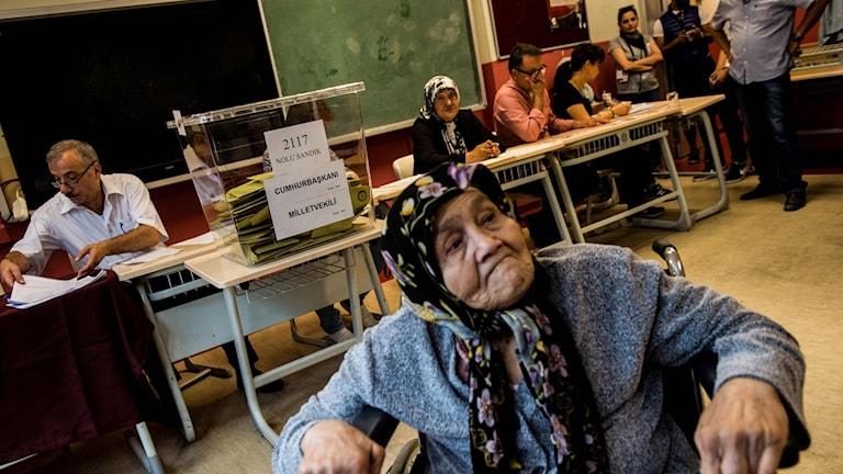 En kvinna väntar i en vallokal. Foto: Yasin Akgul/TT.