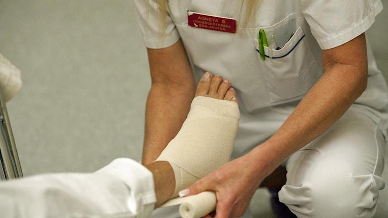 En undersköterska på akuten på Södersjukhuset lindar foten på en patient Foto: Leif R Jansson/Scanpix.