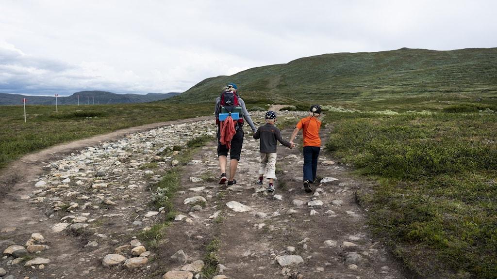 En familj vandrar i fjällen